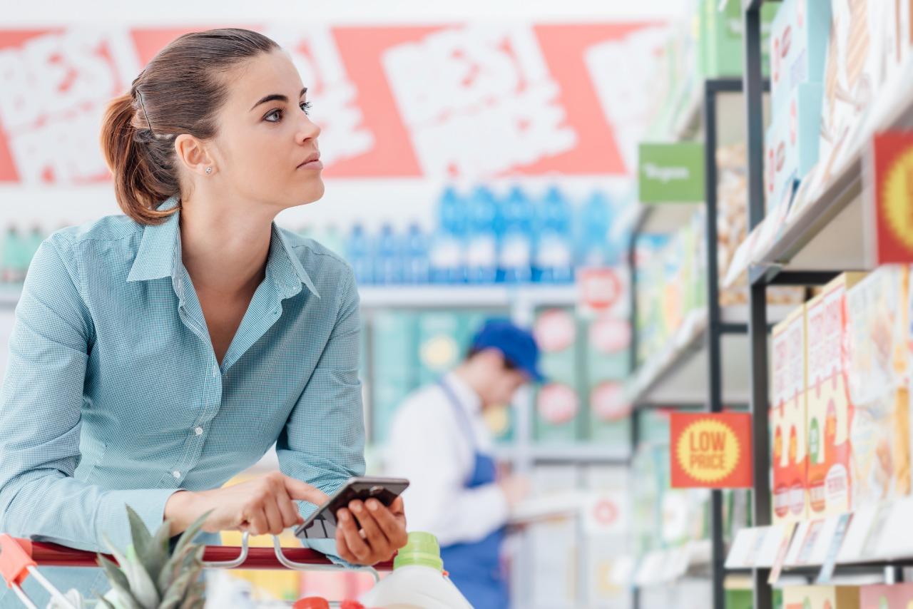 cliente caminhando em supermercado com celular na mão